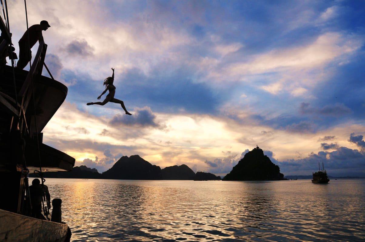 Kvinde i sort silhuet hopper ud i vandet i Ha Long Bay