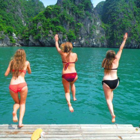 Tre kvinder hopper ud i vandet i Ha Long Bay