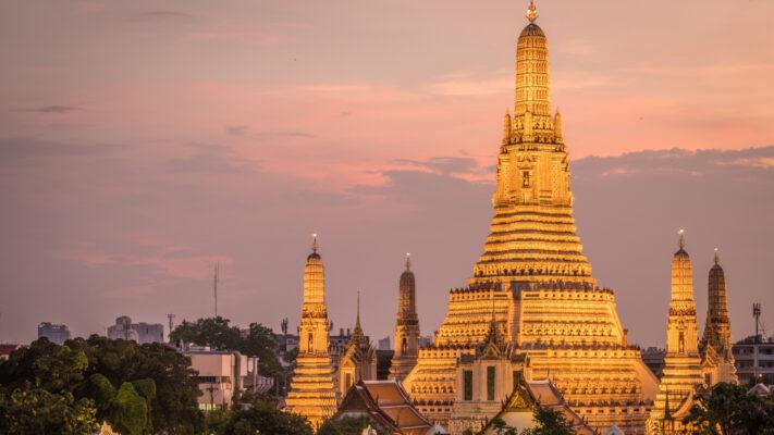 Gylden bygning i Thailand i solnedgang